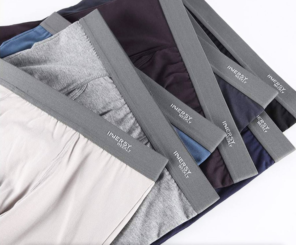 7 pairs of men's boxers laying on top of each other in a variety of grey, black, and blue shades