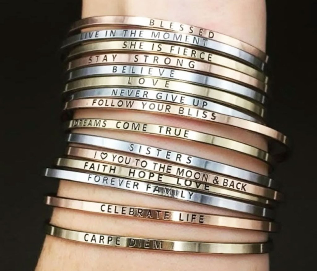 woman's wrist with a ton of thin metal bracelets with inspirational signs on them in gold, silver, and rose gold colors