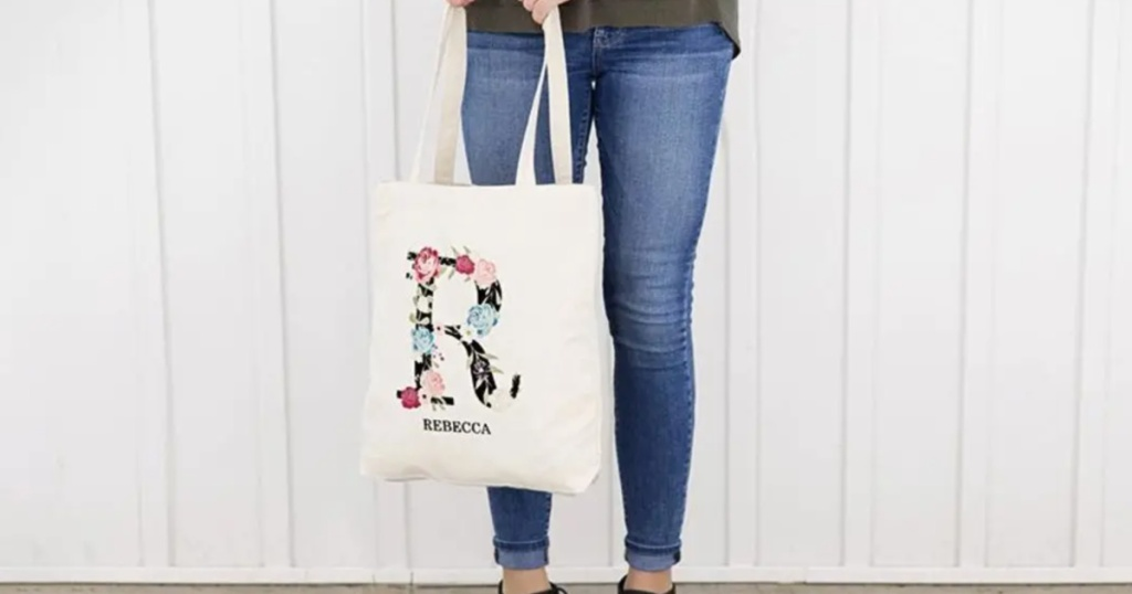 woman standing outside wearing jeans holding a monogrammed tote bag