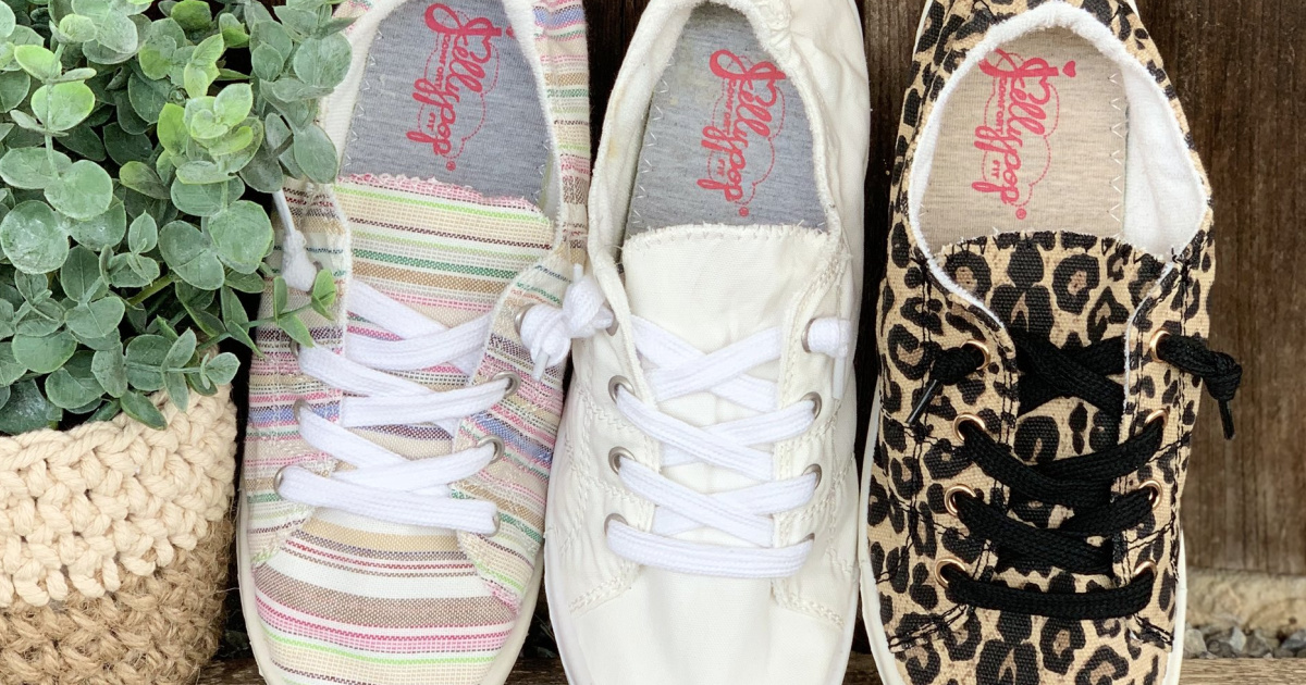 three styles of women's sneakers standing up against wall next to plant