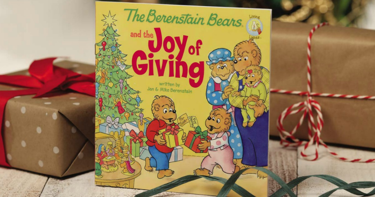 the joy of giving book in front of a tree with presents