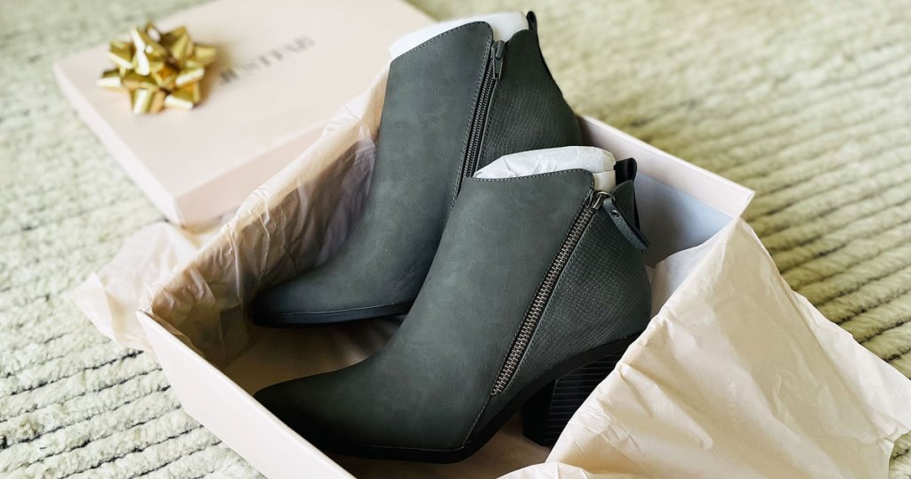 pair of grey booties in a pink shoe box
