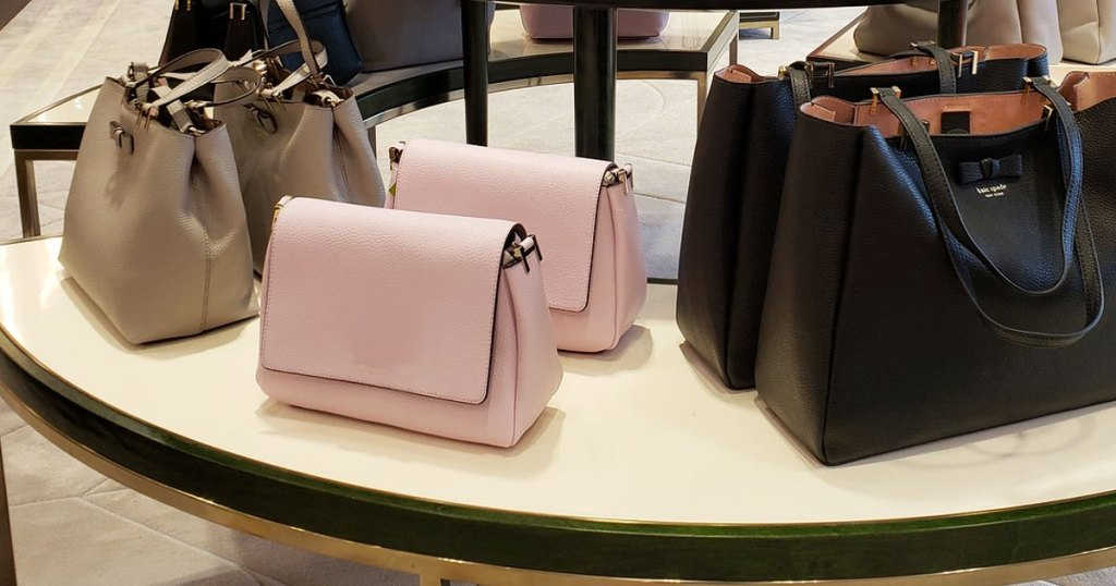 brown, light pink, and black kate spade bags on display table at store