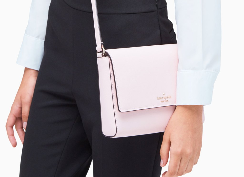 woman in black high waisted pants with light pink kate spade crossbody at her hip