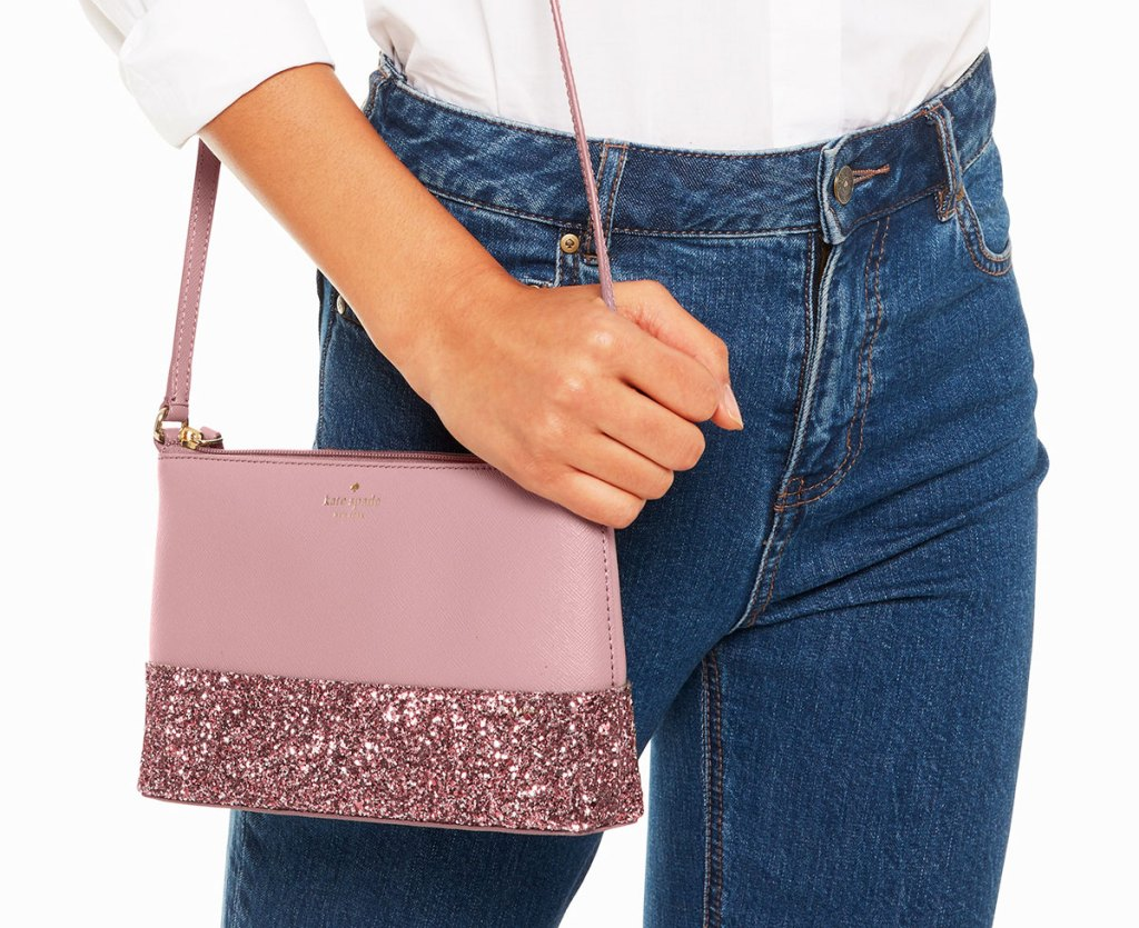 woman in high wasited jeans with a pink kate spade crossbody with pink sparkles at the bottom