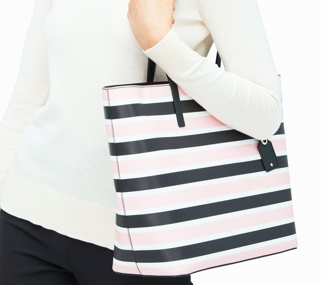 woman in white top with a light pink, white, and black striped kate spade tote bag on her shoulder