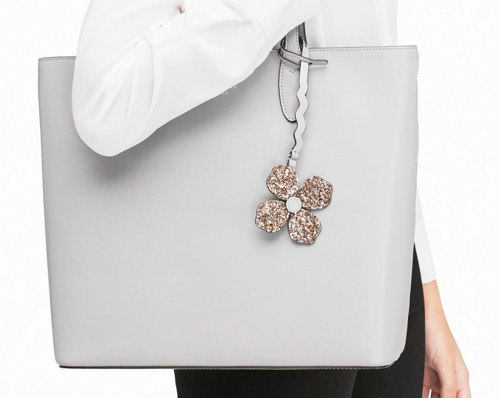 woman in a white sweater with a light grey tote bag on her shoulder with a sparkly flower shaped charm on it