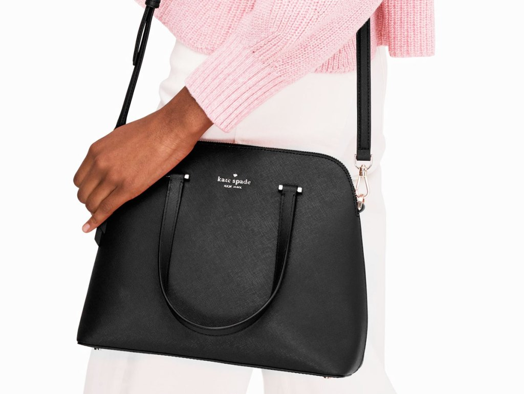 woman in pink weather and white pants with black kate spade crossbody on hip