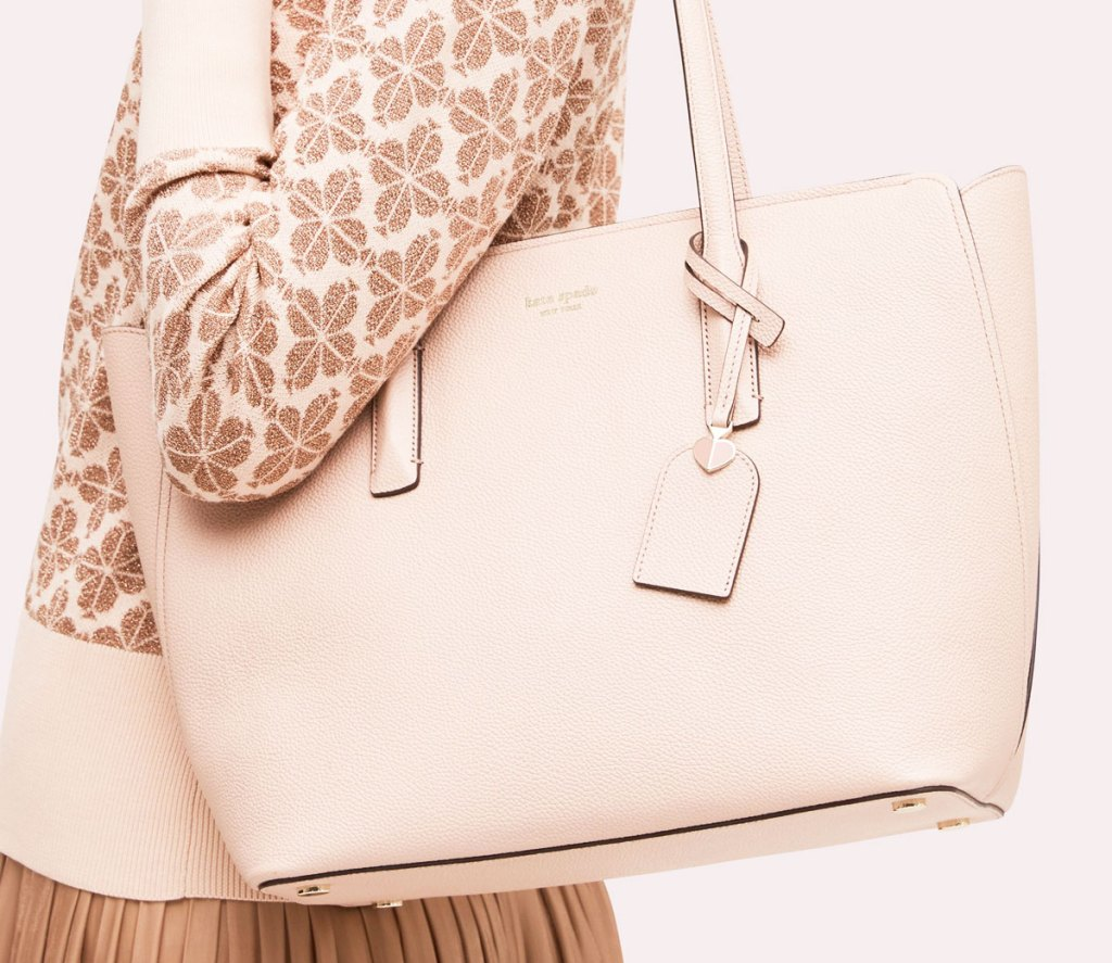 woman in a printed cream colored sweater with a cream colored large kate spade tote on her shoulder
