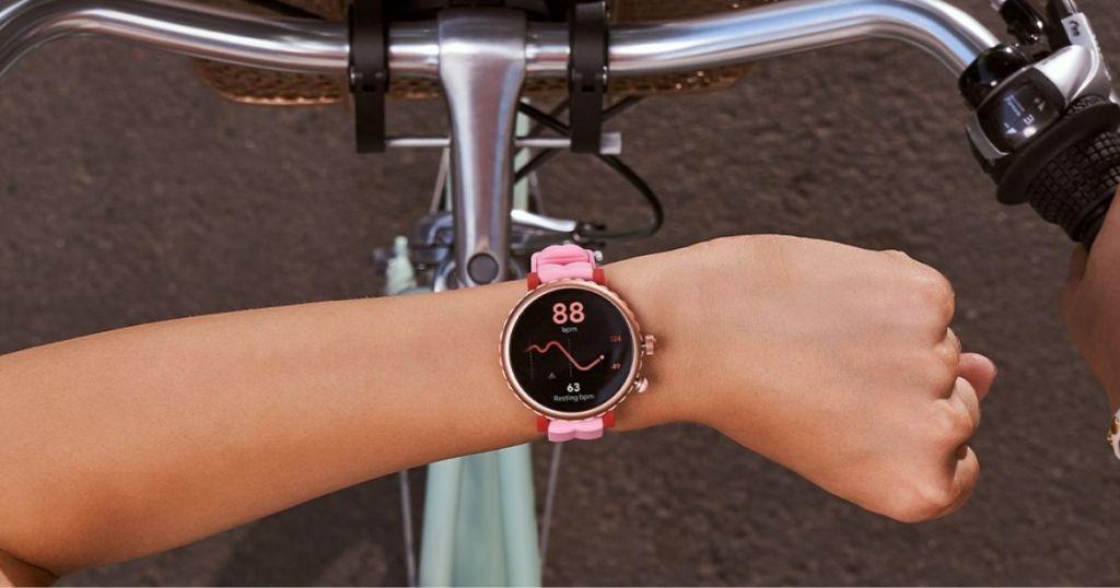 orang yang memakai Smartwatch Kate Spade merah muda di atas sepeda