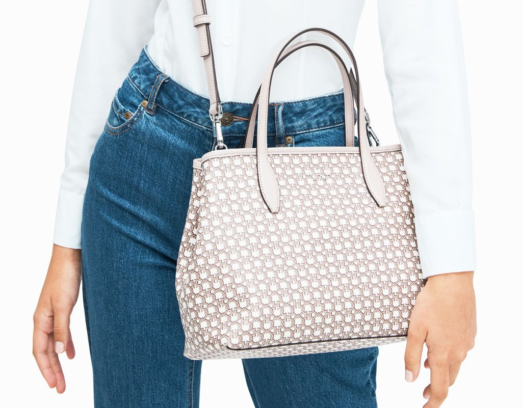 woman in high waisted jeans with cream colored tote bag with an allover spade print