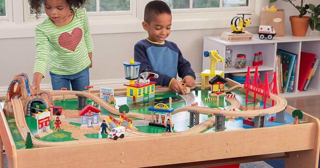 2 anak bermain dengan set meja kereta kayu besar