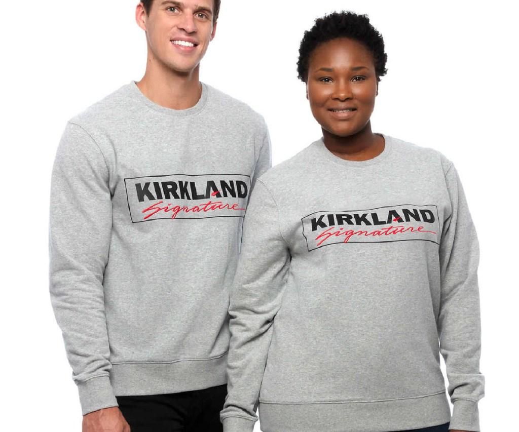 man and woman in gray logo sweatshirts