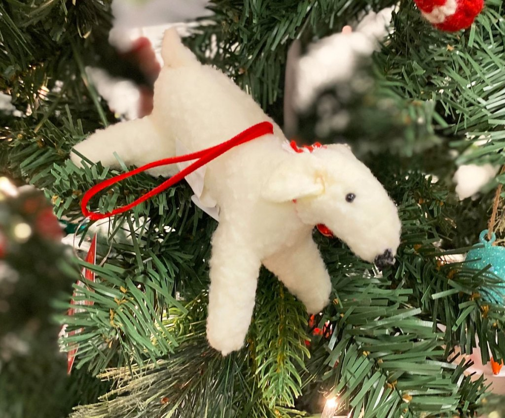 white wool dog shaped ornament on a christmas tree