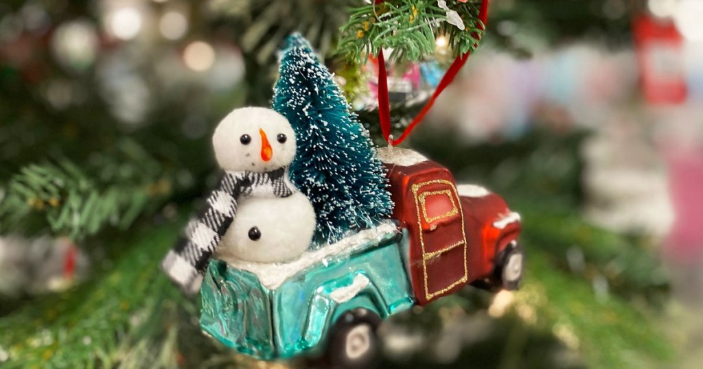 green and red truck ornament with christmas tree and snowman in back hanging on a christmas tree