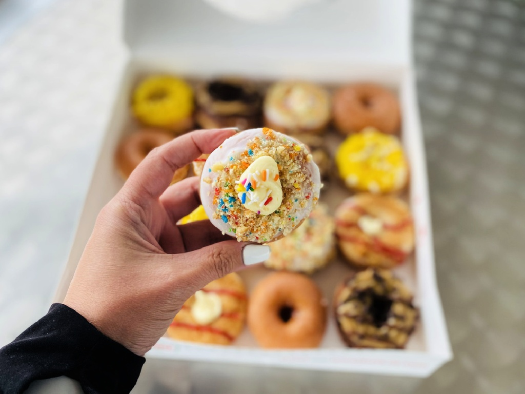 Krispy Kreme Birthday Cake Dessert Mini Doughnuts in hand