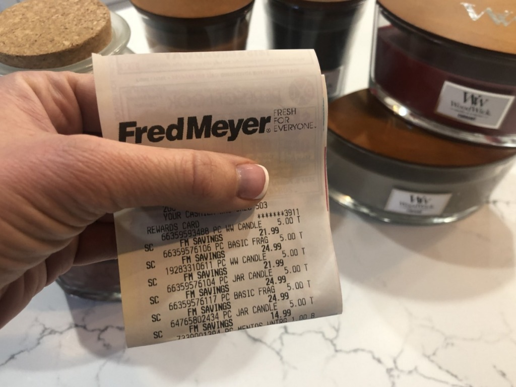 Girl holding fred meyer store receipt showing candle sale