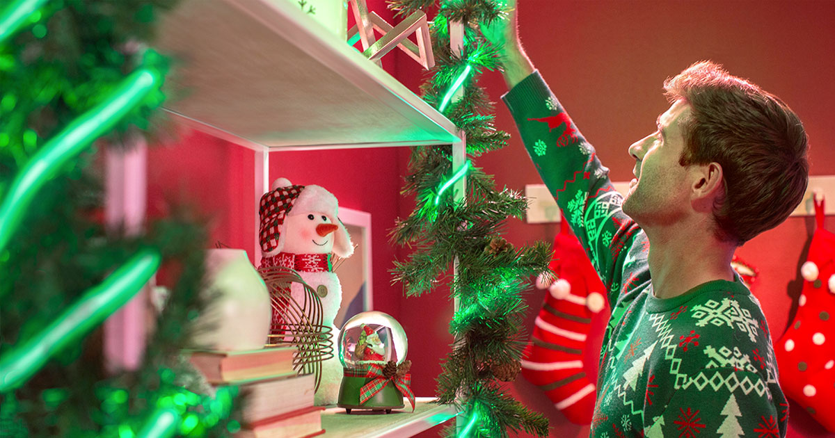 man in christmas sweater reaching something on a bookcase that has been wrapped in christmas greenery and green led strip lights