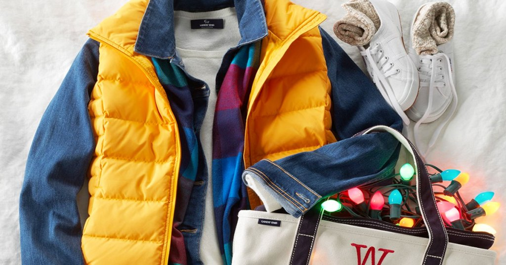 women's denim jacket with a yellow puffer vest over it laid out on a blanket with sleeves of jacket carrying a canvas tote filled with christmas lights