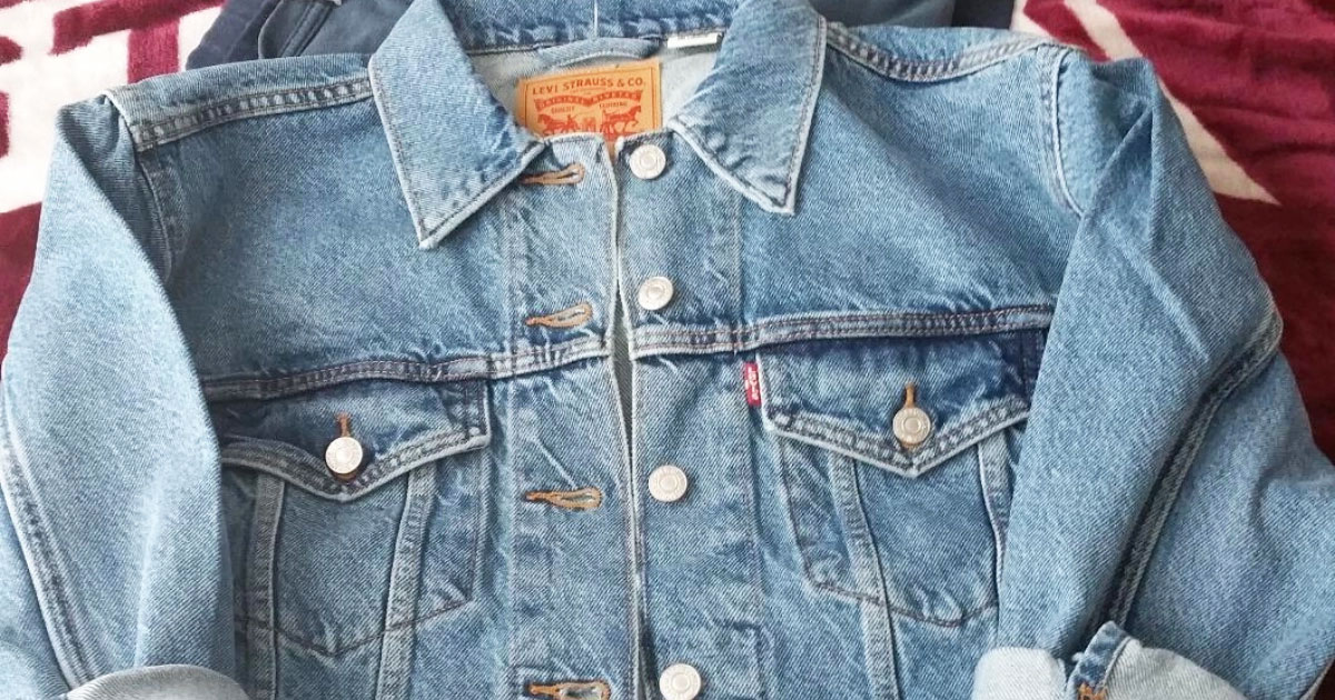 light wash women's levi's denim jacket laying on a bed