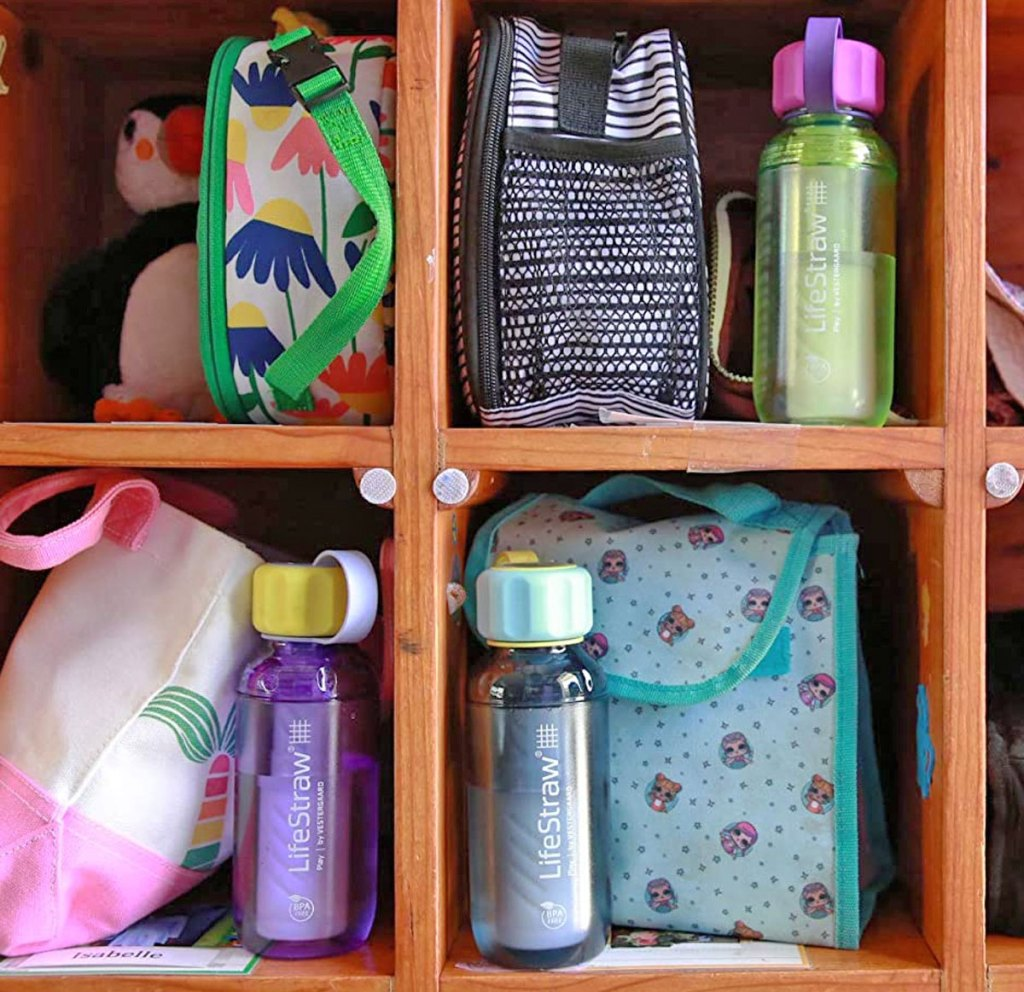 kid lunch boxes and lifestraw water bottles in wooden cubbies