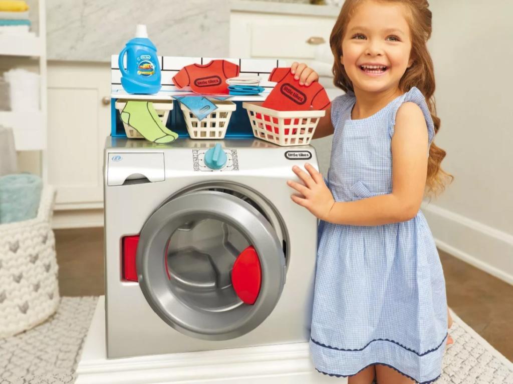 little girl kneeling next to Little Tikes Washer/dryer