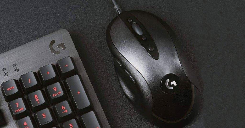 black logitech mouse on a black mousepad next to a black logitech keyboard