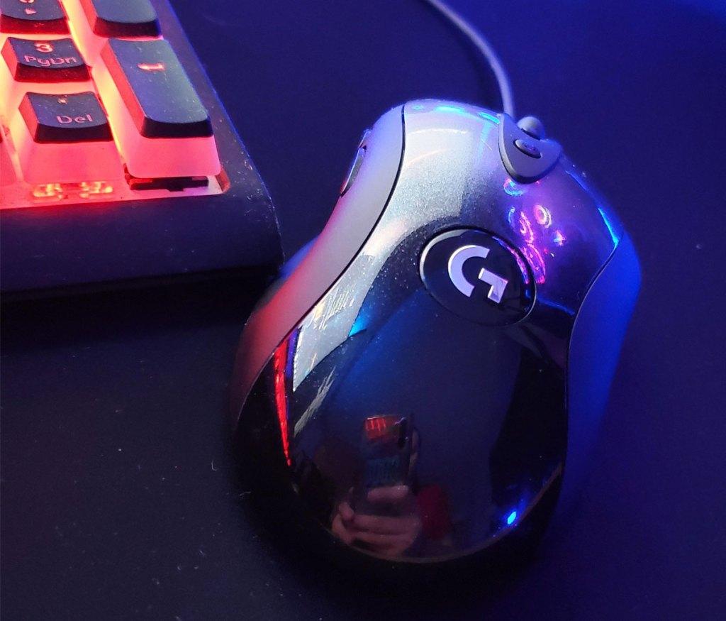 black logitech mouse on a black mousepad near an rgb gaming keyboard