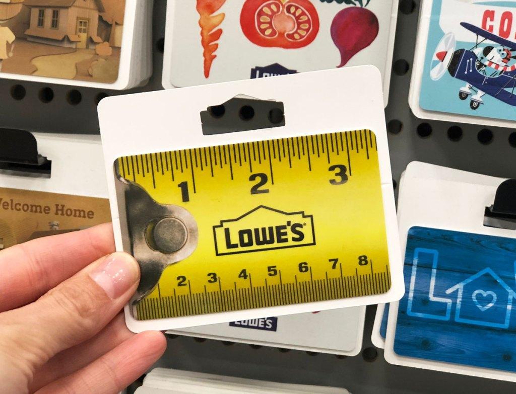 orang yang memegang kartu hadiah lowe yang terlihat seperti pita pengukur