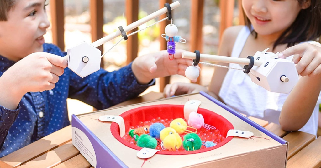 boy and girl playing with fishing educational game on table outside