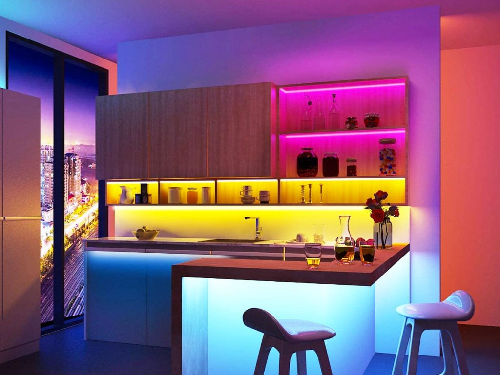 home bar area with cabinets and under countertops light up by led strip lights in various colors