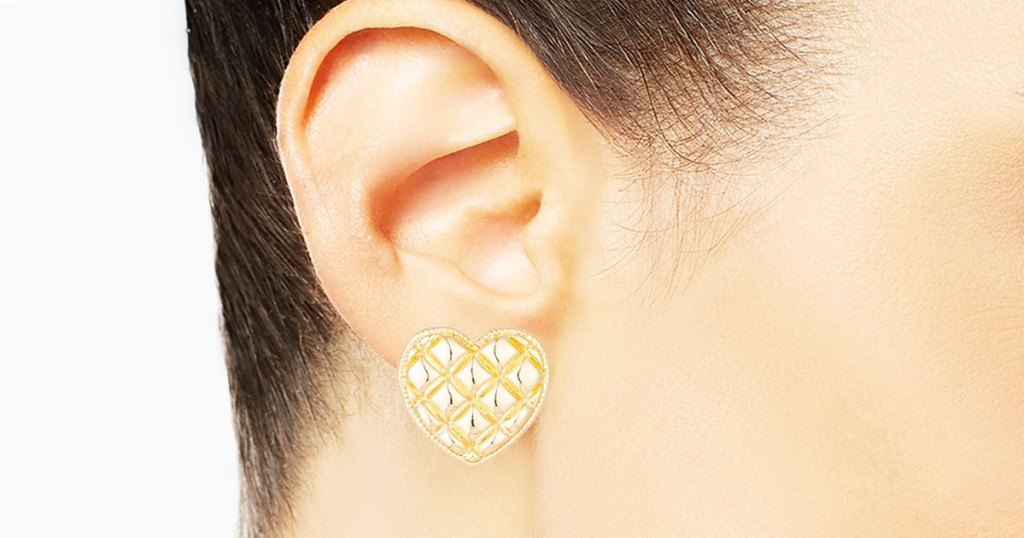 woman wearing a gold quilted patterned heart shaped earring