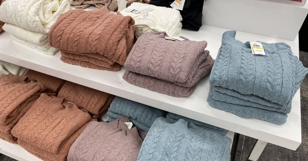 display of sweaters on a table at Macy's