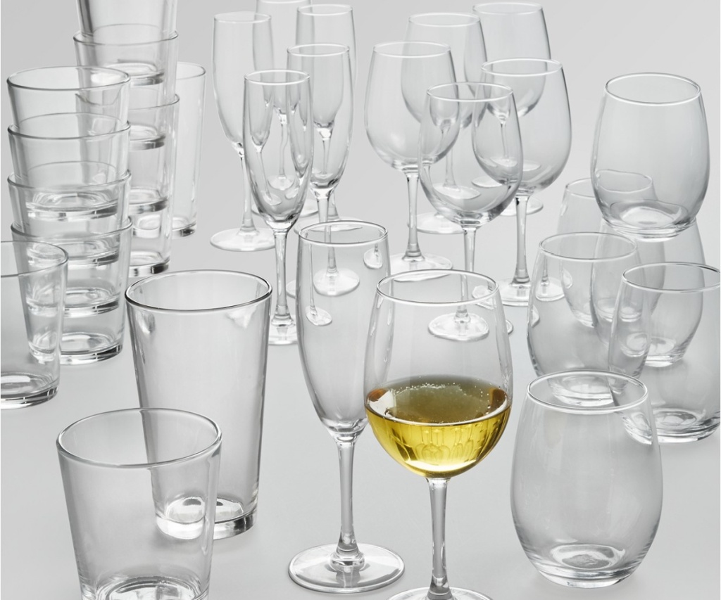 various wine glasses and tumblers and one wine glass filled with white wine