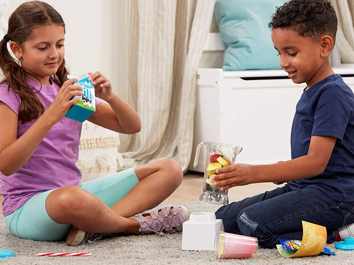 2 kids sitting on the floor playing with a melissa and doug smoothie set