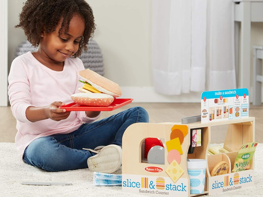 little girl sitting on the floor playing with a melissa and doug sandwich counter set
