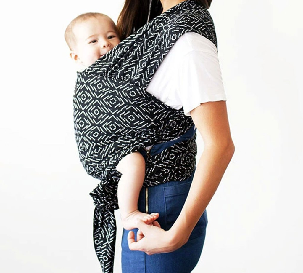 woman standing with baby wrapped to her chest with a black and white printed moby wrap