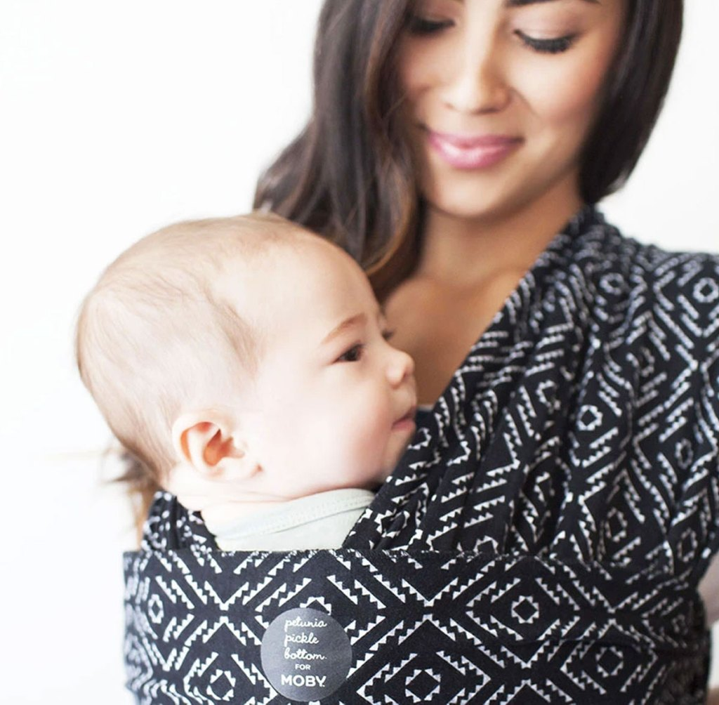 woman with baby at her chest wrapped in and black and white printed moby wrap