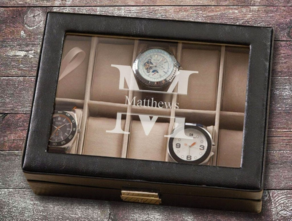 black leather watch box with glass top monogrammed with large M and has three watches inside