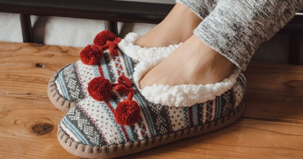 Muk Luks Slippers on a pair of feet resting on a wooden floor