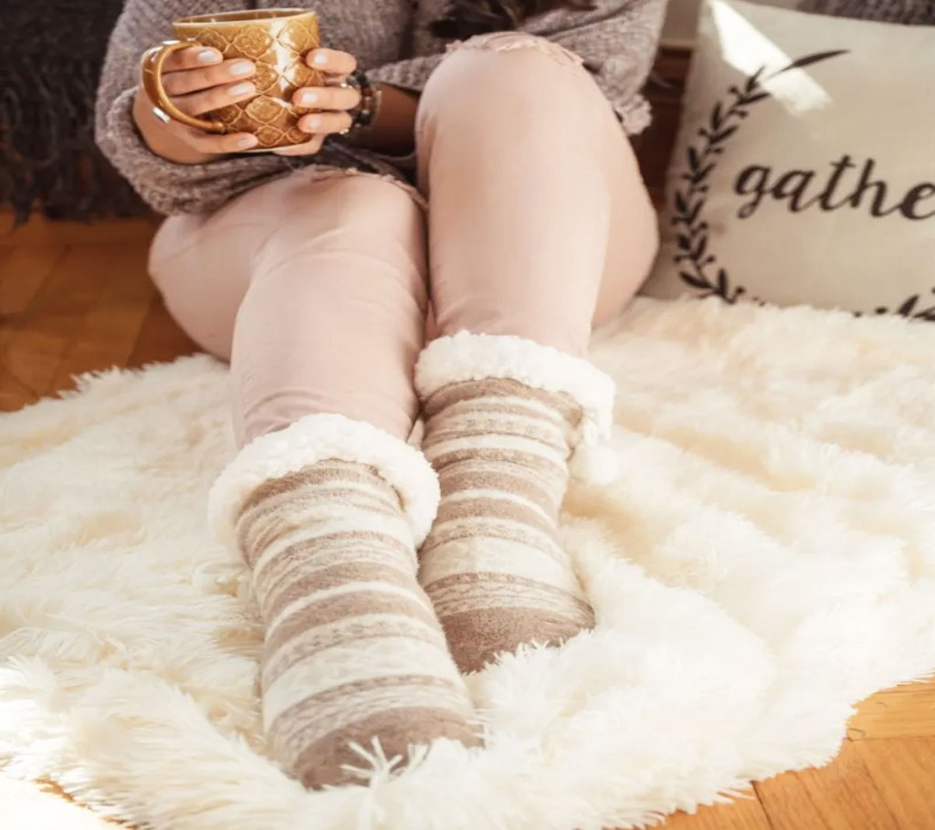 woman sitting on fluffy white rug holding a cup of coffee and wearingpair of cream colored muk luks sherpa socks