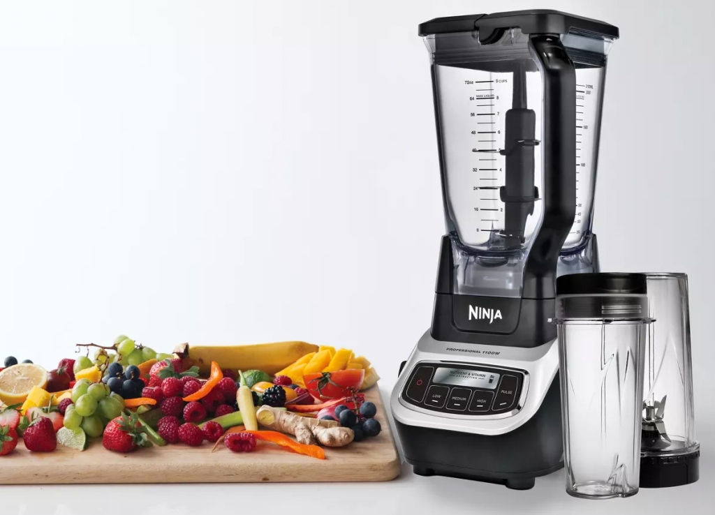 ninja blender with two personal sized blender cups next to cutting board filled with fruits