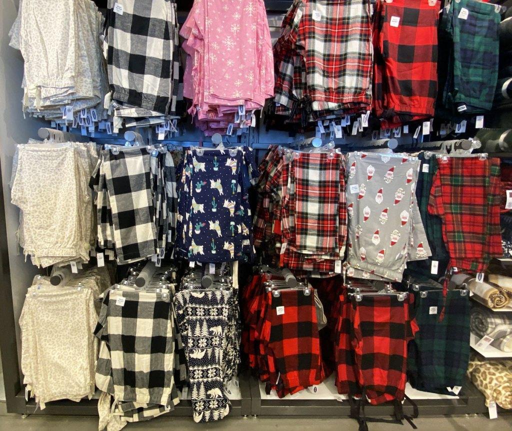 pairs of christmas pajama pants hanging on wall display at old navy