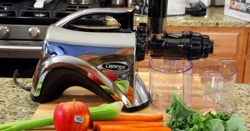 Omega Juicer & Nutrition System on counter with food