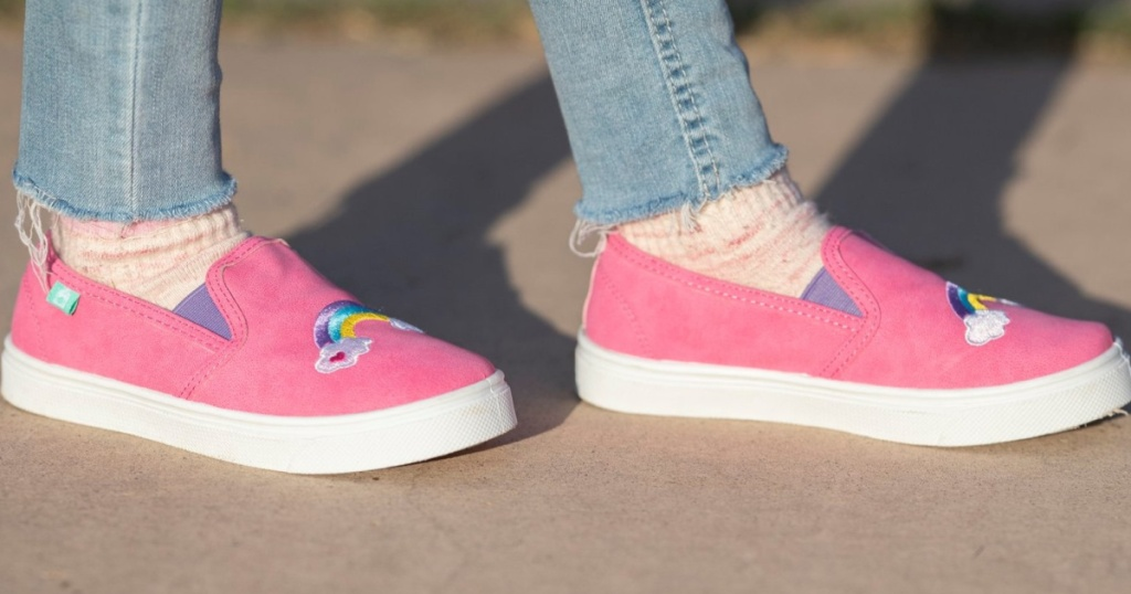 girl wearing bright pink slip on rainbow shoes outside