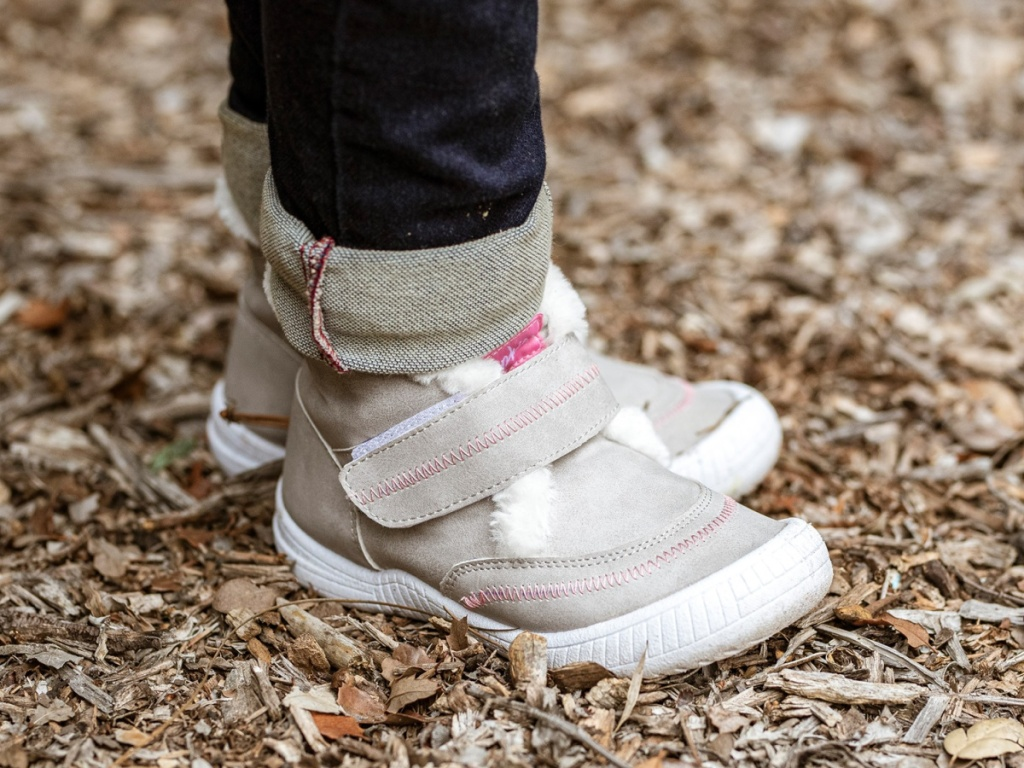 child standing outside wearing grey and pink high top booties