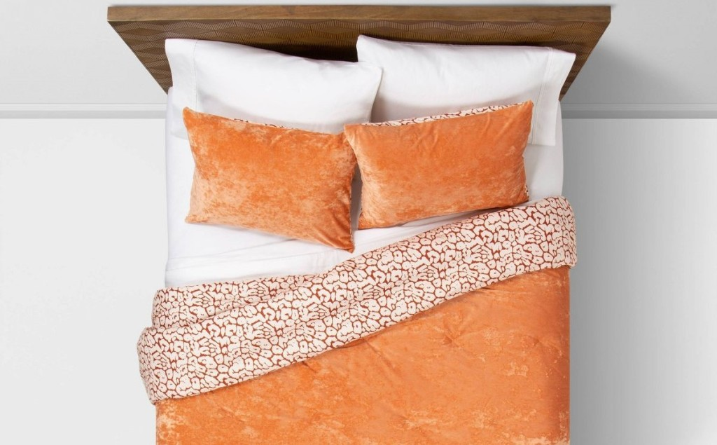 bed with orange comforter on it