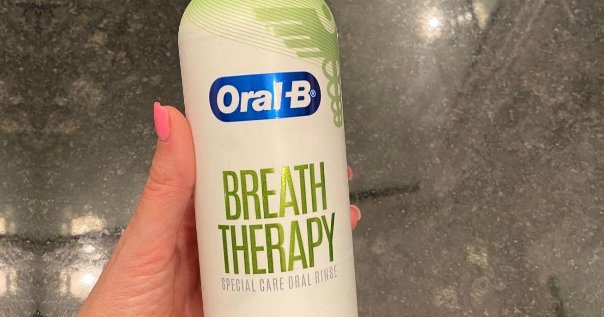 Oral B mouthwash in a bottle in-hand