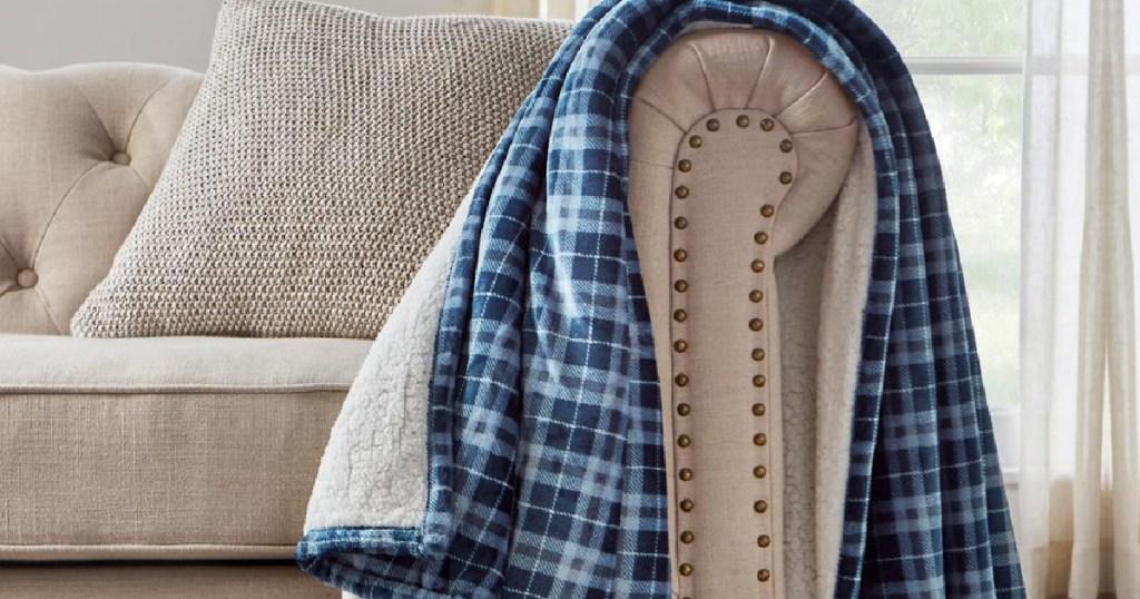 selimut kotak-kotak biru tergeletak di lengan sofa