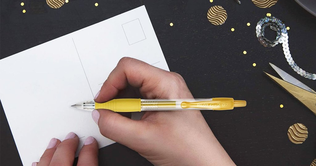 person holding a gold metallic pen to write on a postcard